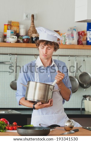Friendly chef preparing  food in his kitchen - stock photo