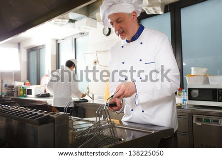 Friendly chef working in his kitchen - stock photo