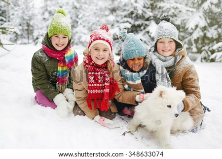 Friendly children playing with fluffy pet in winter park - stock photo