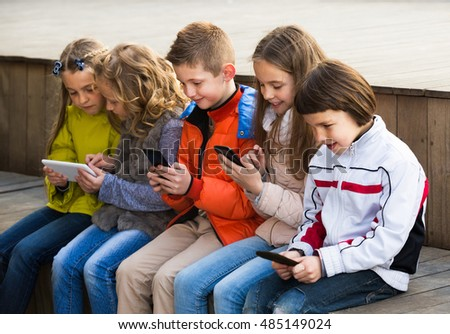 Friendly children sitting with mobile devices in street