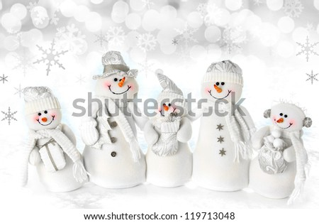Friendly Christmas snowman family on a snow background. - stock photo