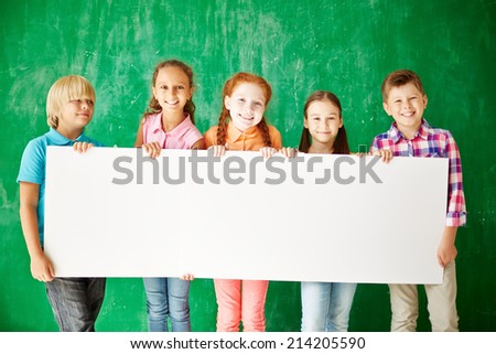 Friendly classmates with blank paper - stock photo