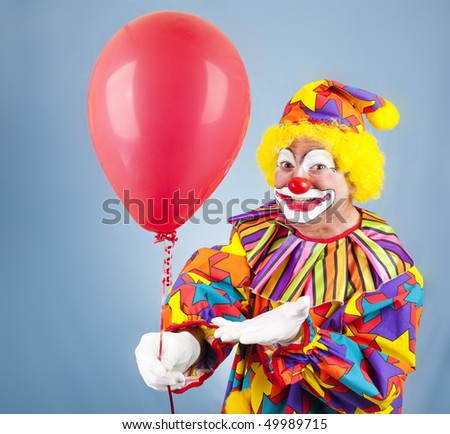 Friendly clown hands you a bright red balloon.
