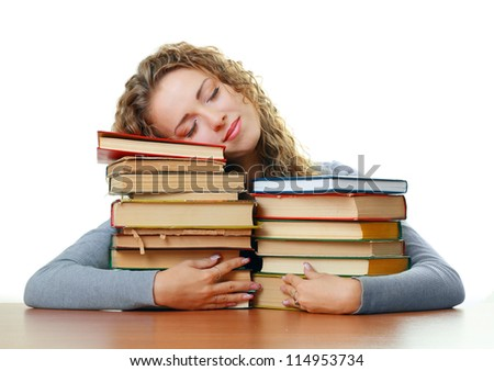 Friendly College student girl sleeping hugging books at the desk isolated