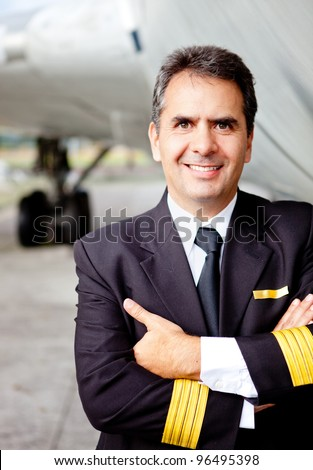 Friendly commercial pilot with an airplane at the backaground - stock photo