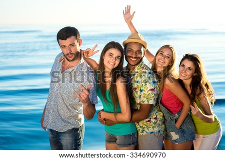 Friendly company posing on sea background. Young people at sea. Trip to the resort. Guys and girls on the background of the sea. - stock photo