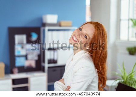 Friendly confident businesswoman standing with folded arms in the office looking at the camera with her head tilted back and a charming smile - stock photo