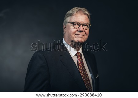 Friendly confident stylish middle-aged businessman wearing glasses posing against a dark background, head and shoulders portrait - stock photo