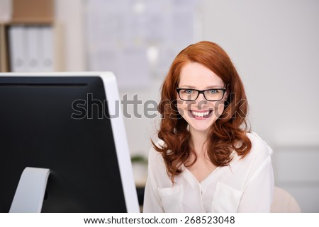 Friendly confident young businesswoman with shoulder length red hair wearing glasses looking at the camera with a beaming happy smile - stock photo