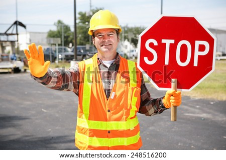 Friendly construction worker in the road holding up a stop sign.   - stock photo