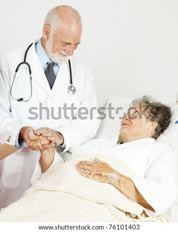 Friendly doctor comforting a senior hospital patient. - stock photo