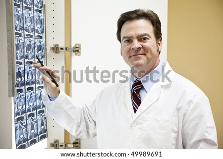Friendly doctor or chiropractor examines a CT scan of a patient's spine. - stock photo