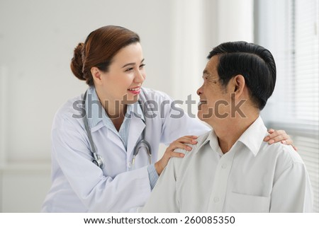 Friendly doctor reassuring senior patient - stock photo