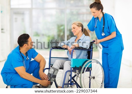 friendly doctor talking to a recovering patient in wheelchair - stock photo