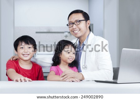 Friendly doctor with children smiling at camera, shot in hospital - stock photo