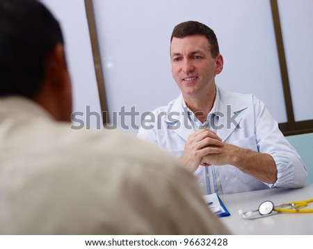 Friendly doctor working and giving assistance to old male patient in hospital office. Focus on background - stock photo