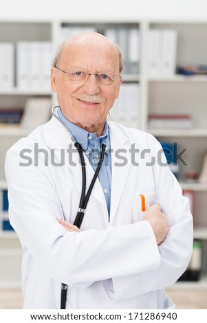 Friendly elderly male doctor with a stethoscope around his neck standing with folded arms in his office or surgery smiling at the camera - stock photo