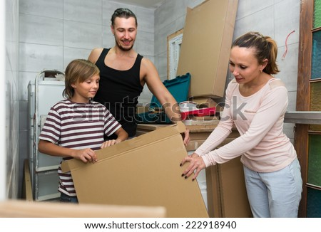 Friendly family of three packing things before relocation  - stock photo