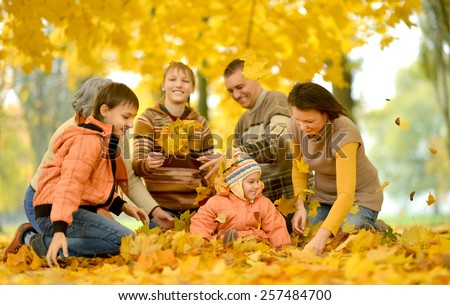 Friendly family on a walk during the fall of the leaves in the park - stock photo