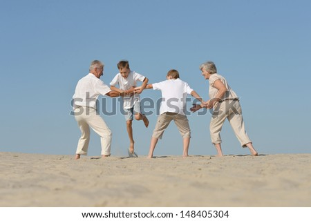 friendly family playing barefoot in the sand in the summer - stock photo