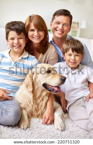 Friendly family with their pet sitting on the floor - stock photo