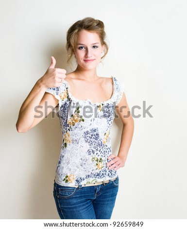 Friendly fashionable young blond woman showing thumbs up. - stock photo