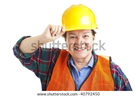 Friendly female construction worker tips her hard hat.  Closeup portrait solated on white.