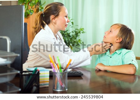 Friendly female doctor checking thyroid of teenager boy patient  - stock photo