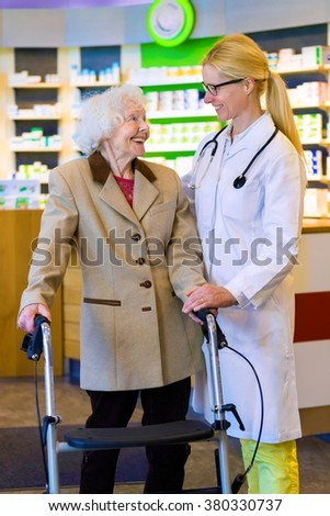 Friendly female doctor with blond pony tail standing with elderly woman using walker in front of pharmacy counter