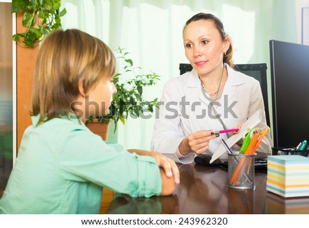 Friendly female doctor with document in hand, talking with teenage patient - stock photo