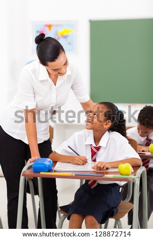friendly female elementary school teacher talking to student in classroom - stock photo