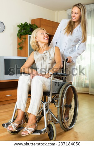 Friendly female nurse and disabled woman on chair communicating indoor - stock photo