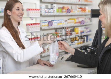 Friendly female pharmacist hands over a plastic sachet with medicine