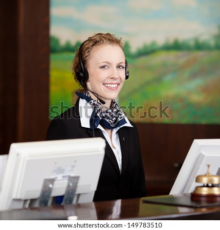 Friendly female receptionist wearing a headset at the reception of the hotel - stock photo