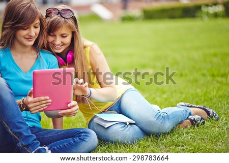 Friendly girls with touchpad networking on green lawn - stock photo