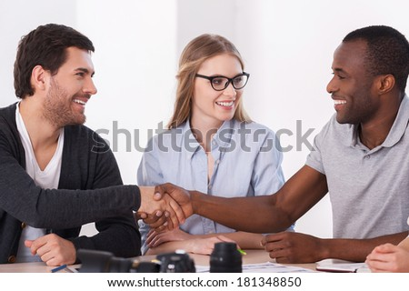 Friendly handshake. Two business people in casual wear handshaking while woman sitting between them and smiling - stock photo
