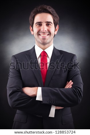 Friendly handsome businessman standing on black background - stock photo