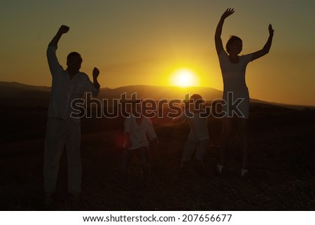 Friendly happy family jumping against the sunset