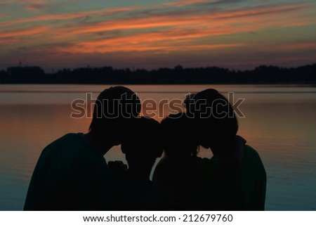 Friendly happy family near the river against the sunset - stock photo