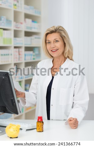 Friendly happy female pharmacist standing behind a computer in the pharmacy holding a prescription and smiling at the camera - stock photo