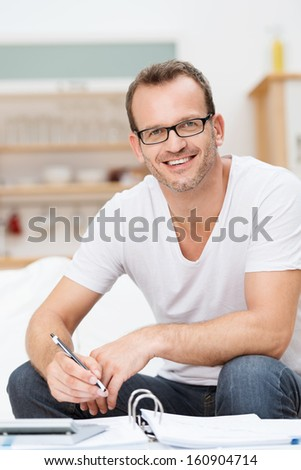 Friendly happy good looking man in glasses relaxing in his living room working on paperwork and his accounts looking up to smile at the camera - stock photo