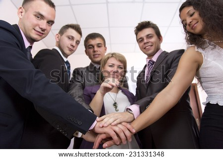 Friendly harmonious business team. Six business people join hands and smiling. Focus is on hands, but face expressions is recognizable.
