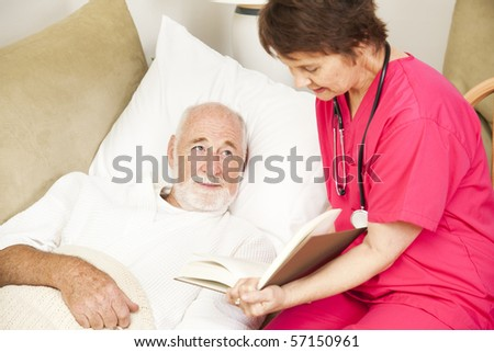 Friendly home caregiver reads to an elderly patient. - stock photo
