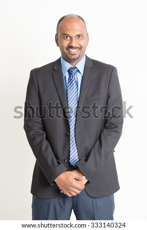 Friendly Indian businessman in formal suit looking at camera, standing on plain background. - stock photo