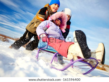 Friendly kids in winterwear having happy time outside - stock photo