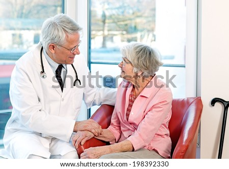 Friendly kind male doctor reassuring an elderly woman patient as they sit together having a consultation in front of a bright window - stock photo