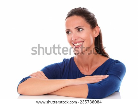 Friendly lady looking to her right, arms crossed in white background - copyspace - stock photo