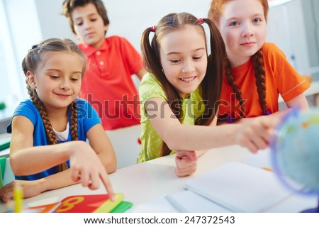 Friendly little girls sitting at lesson in school