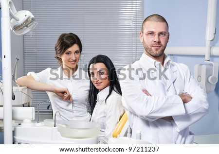 Friendly male dentist, assistant and smiling patient at dental clinic - stock photo