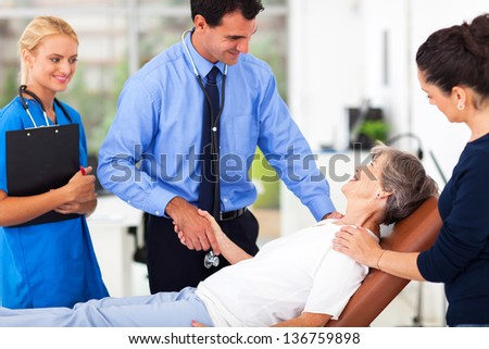 friendly male doctor greeting senior patient before medical checkup - stock photo